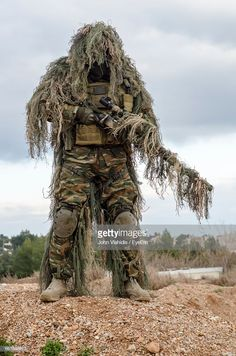 Stock Photo : Army Man In Ghillie Suit With Rifle Standing On Field