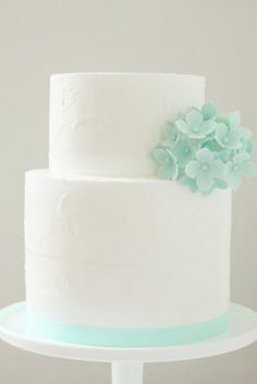 Simple and beautiful white wedding cake with mint green flowers