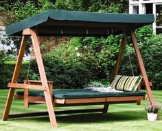 lit suspendu en bois avec matelas et auvent verts