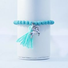 Mooi groen/blauw armbandje met schattig bedeltje en een kwastje
