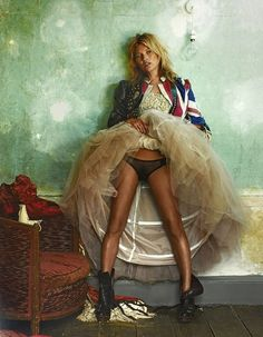 Kate Moss flashes black underwear beneath a lace tutu dress, paired with a vintage leather jacket and black boots.