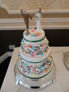 Fruit wedding cake. Bride and groom toppers, with colourful flowers and emerald green ribbon design