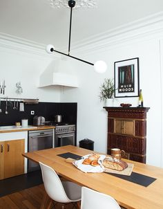 A Two Spheres ceiling lamp from Atelier Areti hangs above the Hansen's dining table, which includes an inset—one side is wood, the other stone.