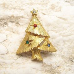 Cute vintage Christmas tree pin sprinkled with tiny rhinestones would be great for a coat lapel or to start your daughter off with her own collection of vintage jewelry. Pretty soft gold tone metal an