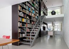 "Beautiful use of space and lots of room for books! ""Epic Trilogy: Bookcase Spans 3 Levels of Renovated Loft  Aligned alongside floating steps that bring you right up next to your favorite volumes whenever you walk up or down, this lovely storage system organizes  space as well as books.  This Rotterdam townhouse is tall and narrow, but by pushing storage to the side, Shift enabled it to feel bright and open with continuously-flowing, open-riser stairs."""