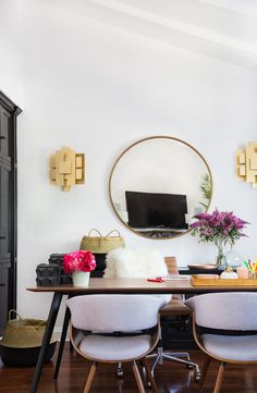 Glam home office with a round mirror, matching gold sconces, and a midcentury modern desk