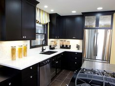 After designer Meg Caswell worked her magic, this space boasts sleek black cabinets and brand new appliances. Recessed and under-cabinet lighting illuminate the contemporary space.