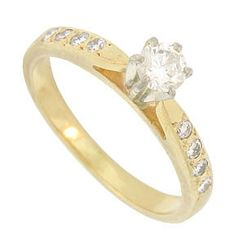 This exceptional 14K yellow gold engagement ring is set with a .27 carat H color, Si2 clarity round diamond. Quartets of sparkling diamonds are set into the rings shoulders. The Retro Modern ring measures 5.20 mm in width. Circa: 1940. Size 5. We can re-size.
