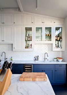 Navy lower cabinets, white upper, white subway tile and marble counter tops.