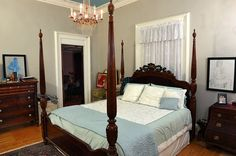 Master bedroom with four poster bed and chandelier