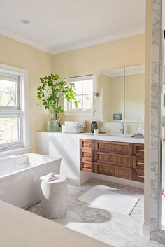Beige-and-white bathrooms make for timeless designs. Straight edges and geometric shapes modernize this neutral bathroom. The beige walls are a happy medium between white marble flooring and warm wood drawers on a contemporary vanity. #bathroomideas #bathroomcolorschemes #beigebathrooms #bathroomdecor #remodel #bhg