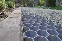 really like this idea - Heavy duty concave pavers to define the edge and aid drainage and honeycomb to keep gravel in place & prevent erosion but still allow drainage.