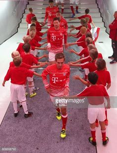 Philipp Lahm Xabi Alonso Franck Ribery and Thomas Mueller of FC Bayern Muenchen walk past children at the players' tunnel before the Bundesliga match...
