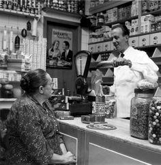 Klant in de winkel bij kruidenier, 1956. De bestelling wordt afgewogen op de weegschaal op de toonbank.