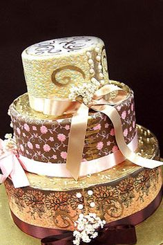 .'  									  								  								  									  										The exquistie three tier round wedding cake is covered and decorated with gold scrollwork and tied with pink, gold and bronze ribbons. Each tier has it's own unique splendor