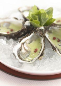 bereiden:Maak de oesters open en vang het sap op. Zet ze koel weg tot verder gebruik. Stoof de sjalotsnippers in een klontje boter. Doe er de gespoelde en gedroogde waterkers bij. Blus met de witte wijn en laat even koken. Doe er de visfumet, de room en de melk bij en laat 5 minuten koken. Mix het geheel met de verse munt en giet door een puntzeef. Roer er het gezeefde oesternat door en breng op smaak met peper en zout.serveren: Lepel wat van de lauwe emulsie over de gekoelde oesters en werk…