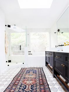 Bright master bathroom with glass shower, black cabinetry, and Persian runner.