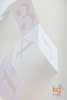 dodatki ślubne pasujące do zaproszeń minimalistycznych w paski, numery stołów
