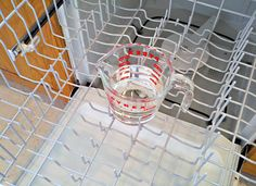 Place a dishwasher-safe cup filled with plain white vinegar on the top rack of the dishwasher. Using the hottest water available, run the dishwasher through a cycle – except for the cup of vinegar, the dishwasher needs to be empty.