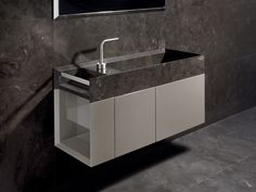 A stylish stone basin atop a cabinet in dove-grey lacquered wood, designed by Rodolfo Dordoni for Salvatori. The name Onsen derives from the Japanese word for hot springs and the Onsen collection celebrates the idea of the bathroom as the centre of wellbeing.   Available in Bianco Carrara, Crema d'Orcia, Pietra d'Avola and Silk Georgette®.