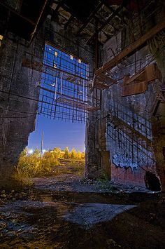 Inside looking out at the large factory building on the long-abandoned Continental Motors Plant in Detroit, Michigan.