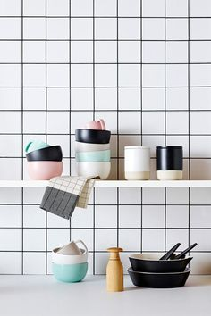 Products stacked on a shelf. Contrasting grout and tiles creates pattern and graphic element - black and white makes pastels pop. country-road-kitchenware