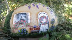 cream colored fairy garden cottage, it has a wagon with claypots, a wreath on the door, Etsy, $26