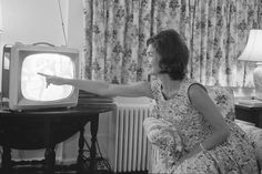 Jacqueline Kennedy sits in the living room of the Kennedy home in Cape Cod pointing to a television after the nomination of her husband, John F. Kennedy for the presidency, on July 12, 1960.