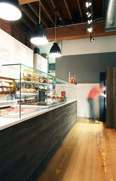 modern product display and sneeze-guard, backpainted glass cabinets for signage, industrial inspired fixtures. Interior design for cafe by bright designlab Portland
