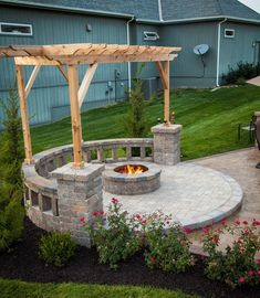 Fire pit with built-in seating, covered by a pergola. Nice little area! #patio #patiolife #outdoorliving #outdoorfireplace #hinklehardscapes