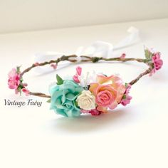 Hi Welcome to Vintage Fairy This flower crown is very delicate, it features lovely soft aqua, pinks and white roses. Gathered lace and cream and pink pearls embellish the centre bouquet.Circle of pink berries gives this crown a feminine lookThe crown is adjustable in the back with pretty ribbonsmall clusters of flowers sitting both sides of the crown and large cluster in the front. Perfect for spring and sumer events This is adjustable for 2 years and up, if you would ...