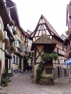 Eguisheim, France I have stood right at this spot and taken a photo of this building - it was raining that day - dark but all around shines. Love visiting this village that is laid out in a circle - you can't get lost! So colorful with flowers everywhere plus a lot of wine tasting rooms.