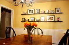 Like the farm table, windsor chairs and simple photo ledges.  Very pretty and simple room.