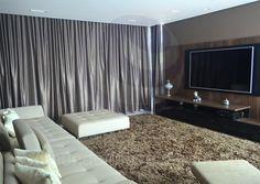 Na sala de TV, um painel em madeira serve como moldura para os equipamentos de áudio e a TV de 75 polegadas de última geração. Longas cortinas de tafetá cinza proporcionam total escuridão ao ambiente, para um melhor efeito home-cinema.