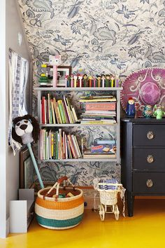 Country Shabby Chic Vintage Wall Treatment: A shelf of books and toys against floral wallpaper.