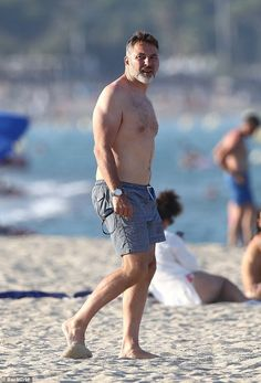 Relaxed: David Walliams, 48, showed off his hunky physique in navy printed trunks as he wa...