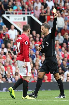 Referee Mark Clattenburg books Wayne Rooney of Manchester United during the…