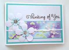 Handmade card constructed from card stock, scrapbook and origami paper, punched flowers, prima flowers, adhesive gems, narrow satin ribbon, stamp it sentiment stamp.