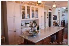I like the white cabinets. Nice spot for a coffee bar?  I like the glass cabinets.  Maybe French style with small window frames? I would want to paint the island.