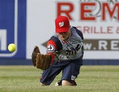 Wounded Warrior Amputee Softball Team outfielder Greg Reynolds dives, and loses, a fly ball during their softball game against the Broome County, New York Law Enforcement team in Binghamton, New York, May 26, 2012.  REUTERS/Gary Cameron