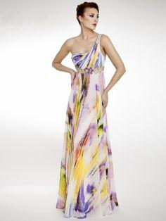 Precioso vestido con un alegre y primaveral estampado, lleno de colores, de corte imperio y escote asimetrico. Adornado con flores bajo pecho y en el tirante.