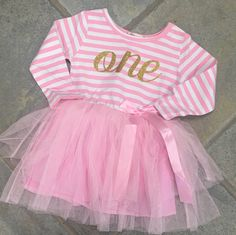 "Elegant birthday pink tutu skirt for baby girls has been created with soft high quality tulle. Hand cut tulle in pink.  Features a gold ""ONE"".         Great for Birthday Parties or a Cake Smash Photo Shoot. So beautiful and these will really make your little one stand out on their big day :) We use gold glitter lettering which really stands out and looks stunning on the dress.          Size 10m-12m    Cotton /Polyester     FREE SHIPPING 