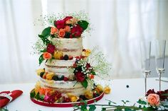 3 tier naked wedding cake decorated with coral and red roses, gypsophilia and seasonal fruit.