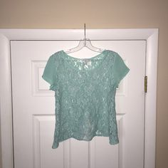 Light Teal Lace Top with Open Back This shirt is in perfect condition! Worn a few times. The shoulder sleeves are sheer, and the front and back of the shirt are paneled with lace. Back has buttons leading down to a small open back. Size is medium! Works with a cami underneath! So beautiful & a gorgeous color! Tops