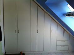Weißer Schrank unter der Dachschräge mit Drehtüren und Schubladen.