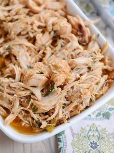 A white dish full of cooked, shredded chicken with bits of cilantro in it.