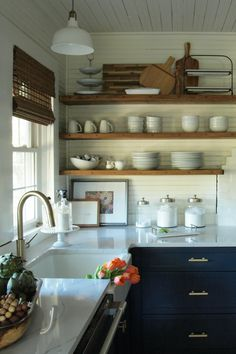 100 year old beach house kitchen reno in Pawleys Island, SC. Navy blue base cabinets, open wood shelving, marble look counters, farmhouse sink, and brass hardware. Check out this stunning design.