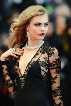 Cara Delevingne wearing black lacy Burberry and posing like shes in a high-end Chopard jewelry campaign.