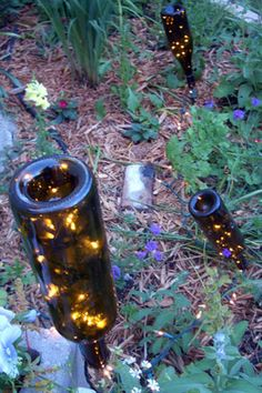 garden lighting Garden Lanterns: A few bottles, Christmas lights, and stakes are all you need to create some magical ambiance in your backyard. Empty Wine Bottles, Lighted Wine Bottles, Bottle Lights, Recycled Bottles, Beer Bottles, Wine Bottle Lighting, Wine Bottle Lanterns, Wine Bottle Fence, Wine Bottle Crafts