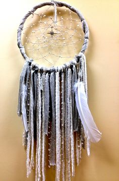 """Beautiful pearl beads on silver thread surrounding an 8-pointed crystal star center.   Silver braided fringe with white feathers adn accents of pearls. (33""""H x 12.5""""W)************************************************************************Dreamcatchers are known to have mystical effects on people's dreams and sleep patterns. Dream Halos are created to enhance your dreamsand filter out negative energies. According to ancient legend,The dream catcher has ..."""